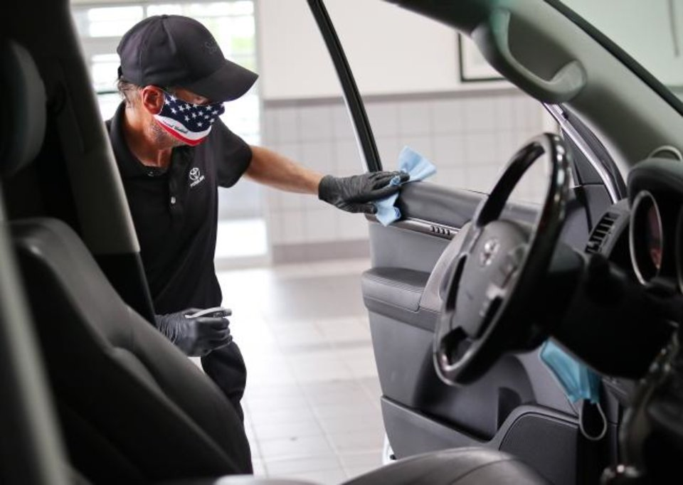 Photo -  Dirk Ness wipes down the interior of a customer's car brought in for service May 14 at Fowler Toyota in Norman. [Doug Hoke/The Oklahoman]