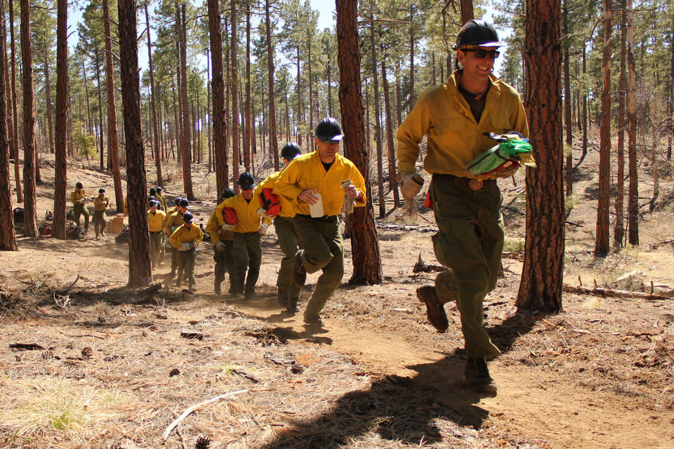 Photo - In this 2012 photo provided by the Cronkite News, members of the Granite Mountain Hotshots run during training on the use of emergency fire shelters. On Sunday, June 30, 2013, 19 members of the Prescott, Ariz.-based crew were killed in the deadliest wildfire involving firefighters in the U.S. for at least 30 years. The firefighters were forced to deploy their emergency fire shelters - tent-like structures meant to shield firefighters from flames and heat - when they were caught near the central Arizona town of Yarnell, according to a state forestry spokesman. (AP Photo/Cronkite News, Connor Radnovich)