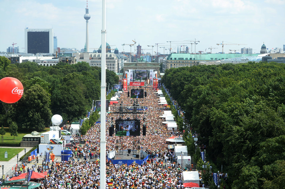 Photo - Soccer fans and supporters of the national soccer squad  gather on the so called  'Fan Mile' near the Brandenburg Gate in Berlin , Tuesday July 15, 2014.  Germany's World Cup winners shared their fourth title with hundreds of thousands of fans by parading the trophy through cheering throngs to celebrate at the Brandenburg Gate on Tuesday. An estimated 400,000 people packed the