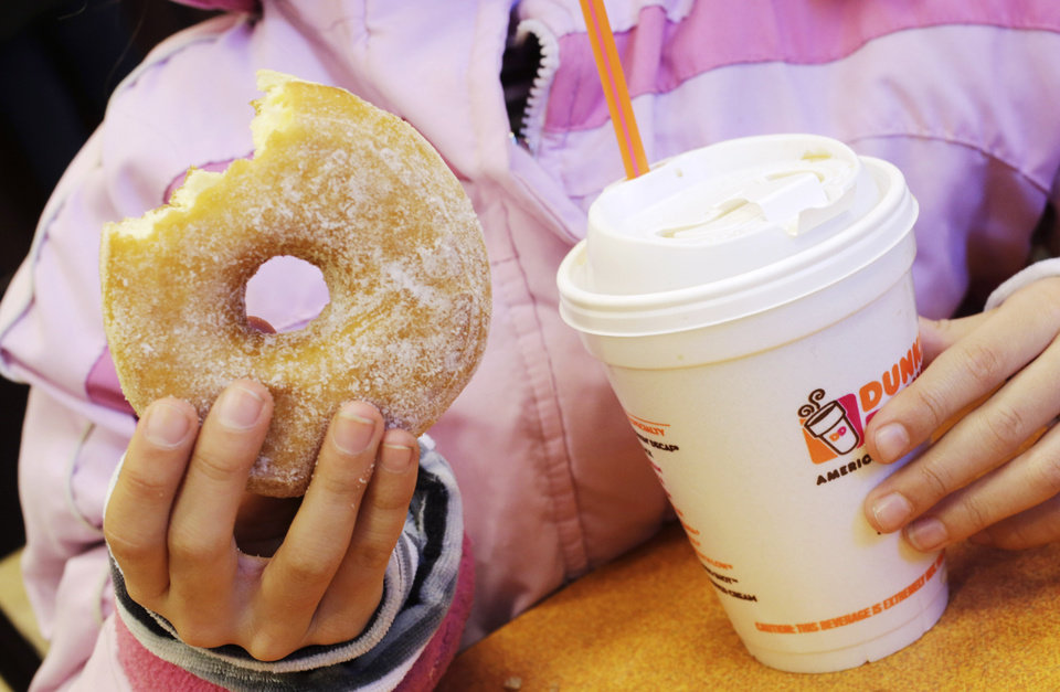 Photo - A girl has a doughnut and a beverage, served in a foam cup, at a Dunkin' Donuts in New York Thursday, Feb. 14, 2013. New York Mayor Michael Bloomberg, who has taken on smoking, sugary drinks and salt, talked about banning food packaging made from polystyrene foam from stores and restaurants in his annual State of the City address on Thursday. (AP Photo/Mark Lennihan)