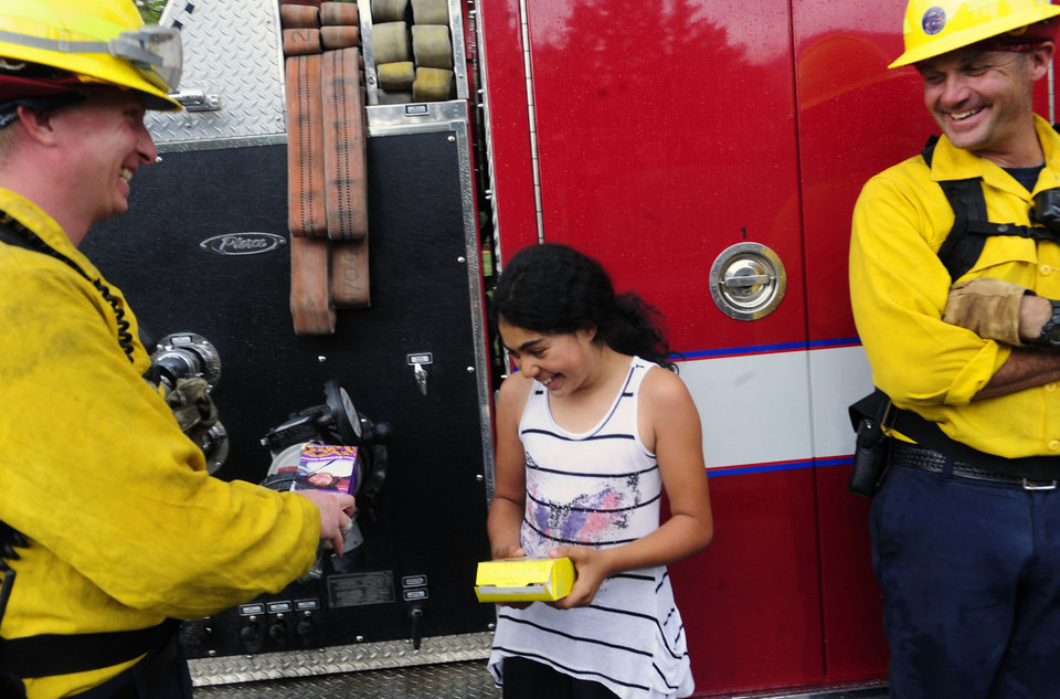 Photo -   Elili Brown, 10, hands out Girl Scout cookies to firefighters Patrick Komitor, left, and Rod Rogers, right, in the Devil's Thumb Subdivision in Boulder, Colo., on Wednesday, June 27, 2012. A Boulder fire and police spokeswoman said a wildfire burning west of Boulder is now within a mile and a half of the city, and fire managers are competing for resources as three major wildfires continue to burn in Colorado. (AP Photo/The Denver Post, Heather Rousseau) MAGS OUT; TV OUT; INTERNET OUT