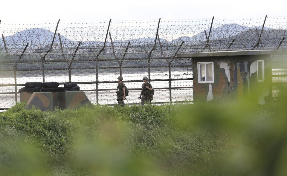 Photo - South Korean army soldiers patrol along the barbed-wire fence in South Korea's Paju, near the border with North Korea, Friday, Aug. 11, 2017. Military officials said Friday they plan to move ahead with large-scale U.S.-South Korea exercises later this month that North Korea, now finalizing plans to launch a salvo of missiles toward Guam, claims are a rehearsal for war. (AP Photo/Ahn Young-joon)