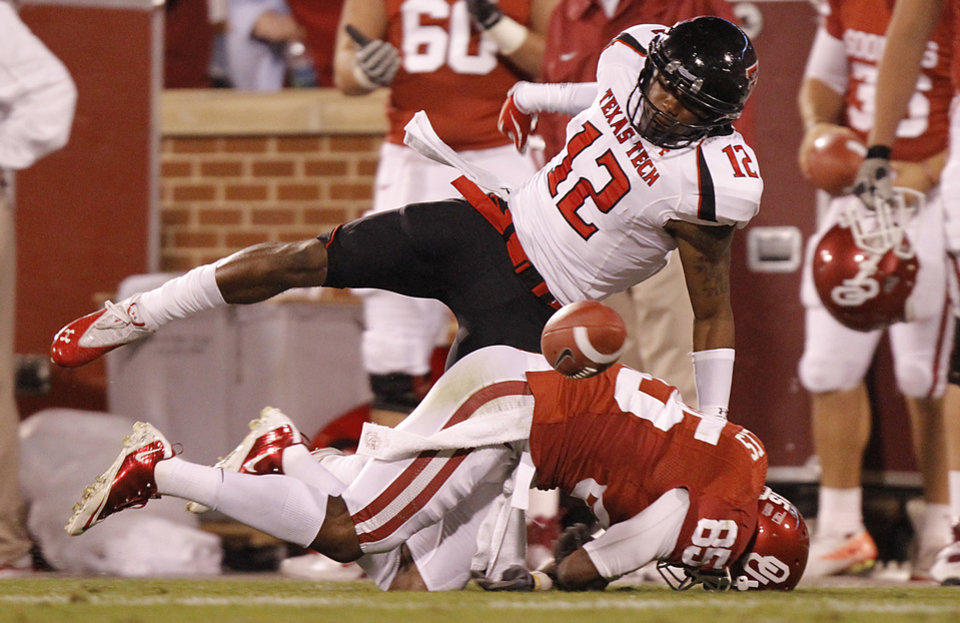 Photo - Texas Tech's D.J. Johnson (12) forces a fumble on Oklahoma's Ryan Broyles (85) during the college football game between the University of Oklahoma Sooners (OU) and Texas Tech University Red Raiders (TTU) at the Gaylord Family-Oklahoma Memorial Stadium on Saturday, Oct. 22, 2011. in Norman, Okla. Photo by Chris Landsberger, The Oklahoman