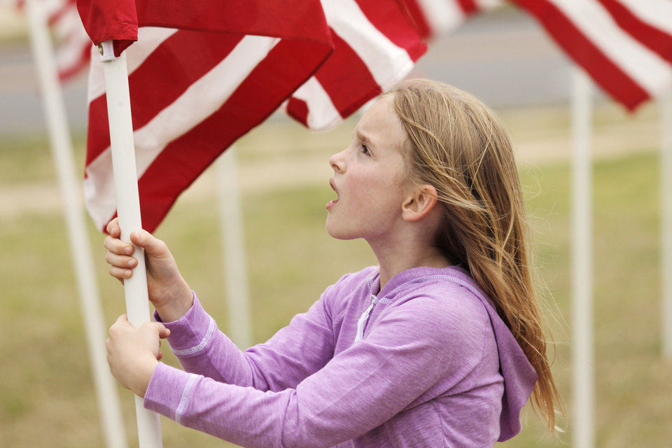 Emma Walker helps to plant American flags in honor of children who died in America in 2011 in the fields south of the state Capitol Sunday, April 7, 2013. Photo by Doug Hoke, The Oklahoman