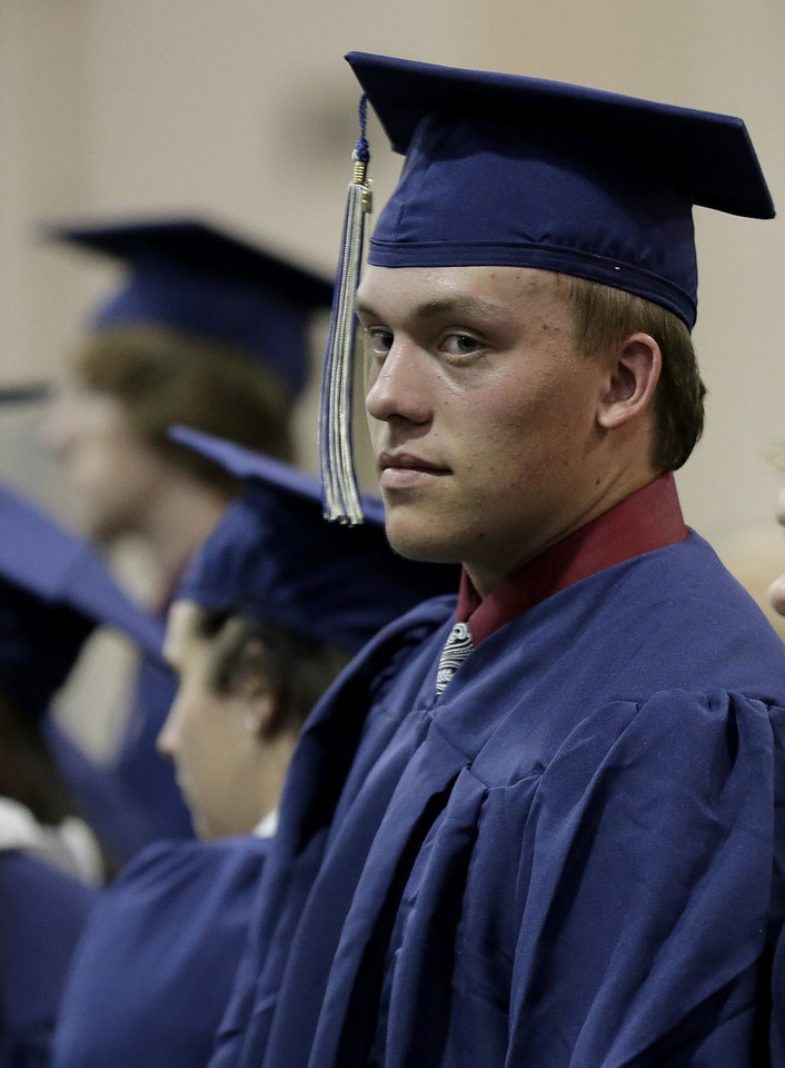 Photo - Southmoore High School senior Jake Spradling waits with his classmates before their commencement ceremony in Oklahoma City, Saturday, May 25, 2013, five days after a tornado wreaked havoc in their attendance area, in Moore, Okla. Spradling's home was among those destroyed after a huge tornado roared through the Oklahoma City suburb Monday, flattening a wide swath of homes and businesses. (AP Photo/Charlie Riedel)