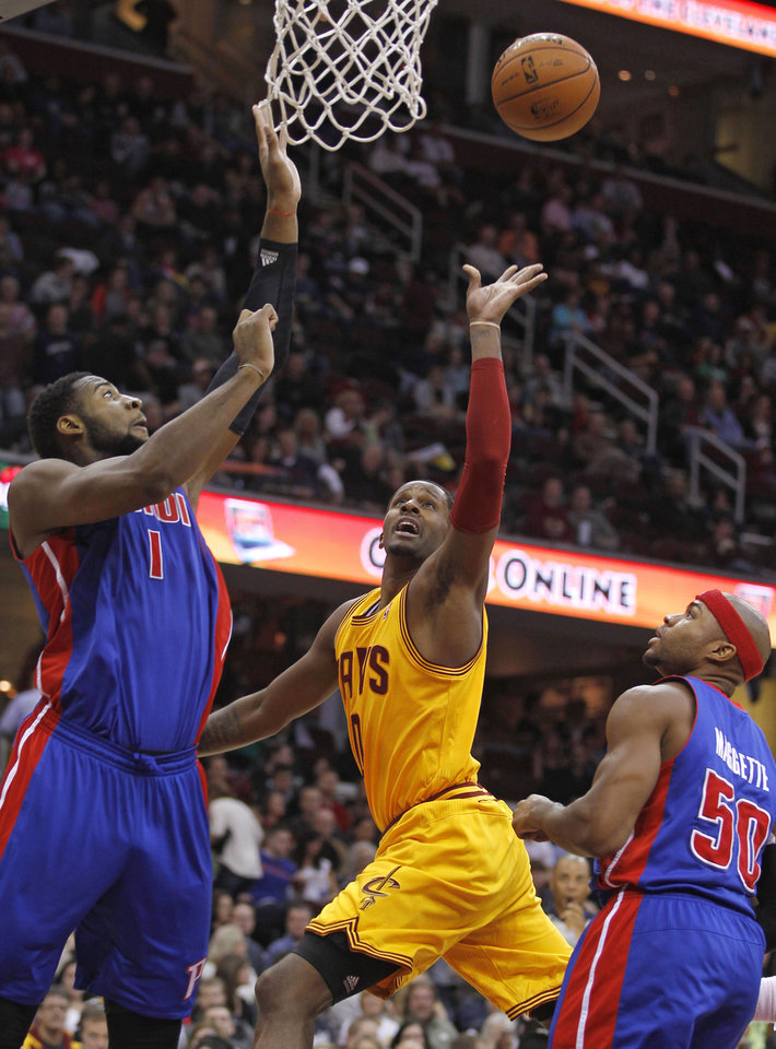 Photo - Cleveland Cavaliers' C.J. Miles, center, shoots over Detroit Pistons' Andre Drummond, left, and Detroit Pistons' Corey Maggette during the second quarter of an NBA basketball game Saturday, Dec. 8, 2012, in Cleveland. (AP Photo/Tony Dejak)