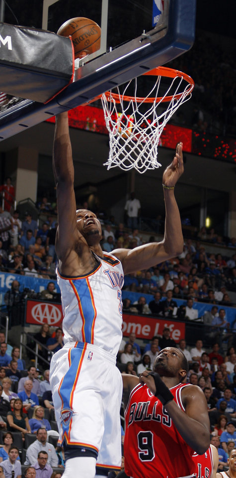 Oklahoma City's Kevin Durant (35) shoots a lay up in front of Chicago's Luol Deng (9) during the NBA basketball game between the Chicago Bulls and the Oklahoma City Thunder at Chesapeake Energy Arena in Oklahoma City, Sunday, April 1, 2012. Photo by Sarah Phipps, The Oklahoman