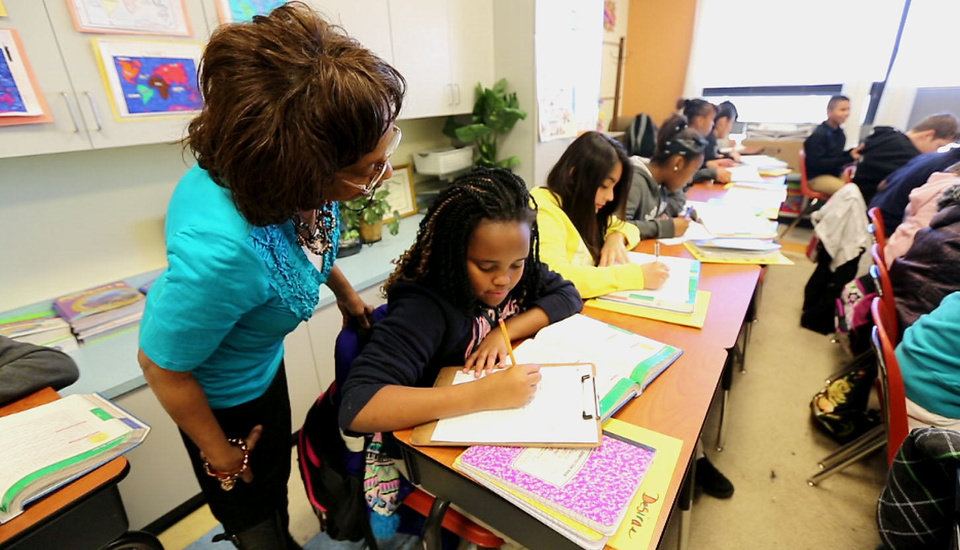 Photo - Britton Elementary School sixth-grade teacher Nadine Smith helps a student with an assignment Thursday. Because of a teacher shortage at the school, Smith has had to add additional students to her class. Photo by Steve Gooch, The Oklahoman   Steve Gooch