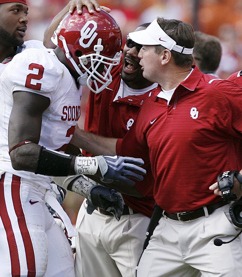 Photo - Oklahoma coach Bob Stoops celebrates with Brian Jackson after his interception during the Red River Rivalry college football game between the University of Oklahoma Sooners (OU) and the University of Texas Longhorns (UT) at the Cotton Bowl in Dallas, Texas, Saturday, Oct. 17, 2009. Photo by Chris Landsberger, The Oklahoman