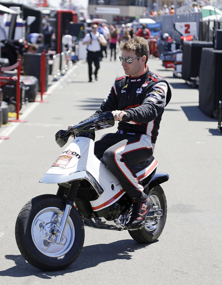 Photo - Will Power, of Australia, rides a scooter to his car in the pit box before the start of practice for the IndyCar auto race Saturday, Aug. 23, 2014, in Sonoma, Calif. (AP Photo/Eric Risberg)