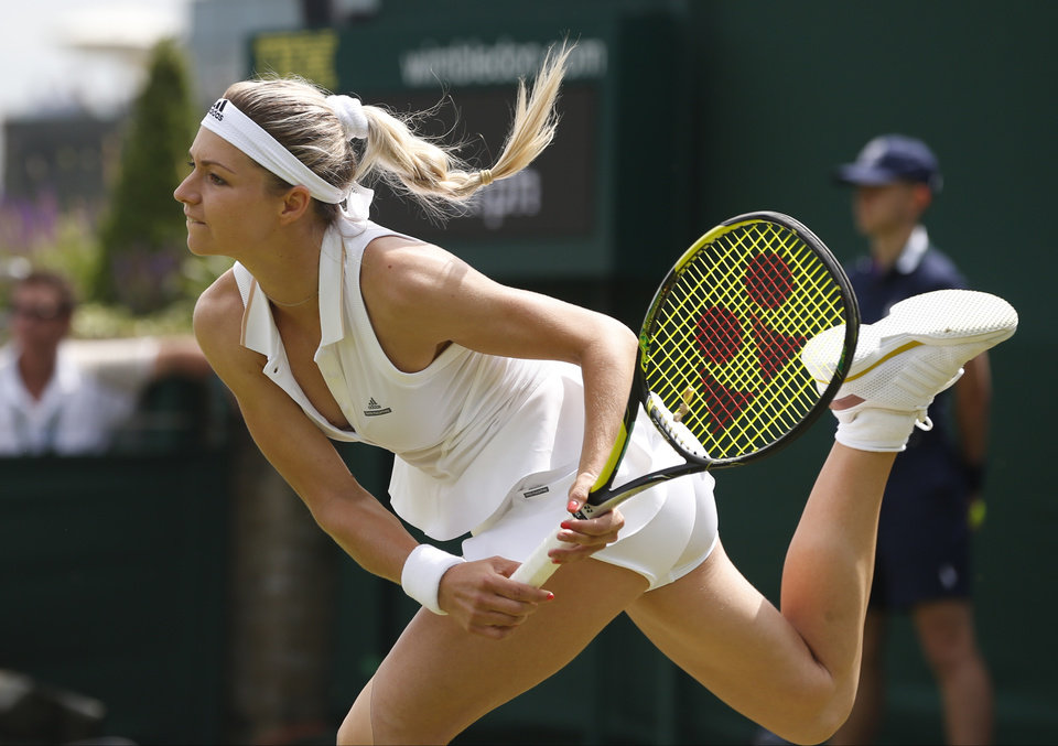 Photo - Russia's Maria Kirilenko plays a return to Sloane Stephens of the U.S. during their first round match at the All England Lawn Tennis Championships in Wimbledon, London,  Monday, June  23, 2014. (AP Photo/Pavel Golovkin)
