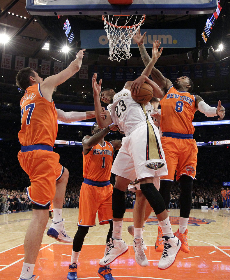 New York Knicks forward Andrea Bargnani, left, of Italy, and New York Knicks guard J.R. Smith (8) defend as New Orleans Pelicans forward Anthony Davis (23) pulls down a rebound in the first half of an NBA basketball game in New York, Sunday, Dec. 1, 2013. The Pelicans won 103-99, but Davis left the game in the first half with a fractured hand. New York Knicks forward Amar'e Stoudemire (1) defends from the floor. (AP Photo/Kathy Willens)