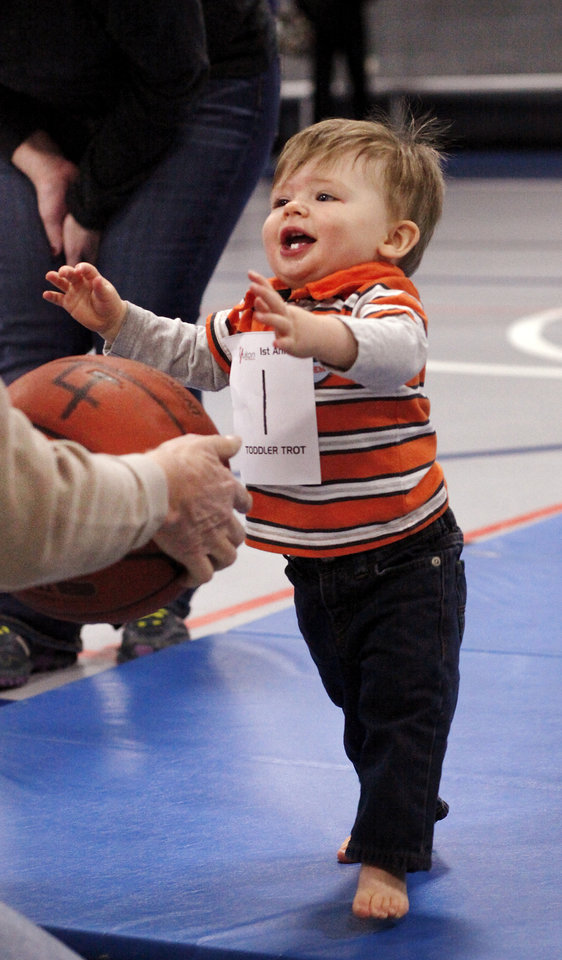 Cooper Ferrell, 1, takes the last steps toward the finish line as he reaches to grab a basketball held by his grandfather. Cooper was the only walking toddler entered in his division, but he competed and walked required distance on the mat to claim his ribbon. Diaper Dash / Baby Crawl contest at Jackie Cooper Gym in Yukon, Saturday, Jan. 5, 2013. Organizers said nine entries registered to compete in the three categories. Age divisions were six to nine months old; 10 to14 months-old; and walking toddlers. Winner in the youngest category was Liam Sorrels, eight months. Winner of the middle category was Shiloh Meiki, 11 months, and the lone entrant in the walking toddler category was Cooper Ferrell, i year old. The contestants raced individually and were timed by judges. The babies were required to crawl from one end to the other on a 20 foot mat. Quickest time was awarded first place. Photo by Jim Beckel, The Oklahoman