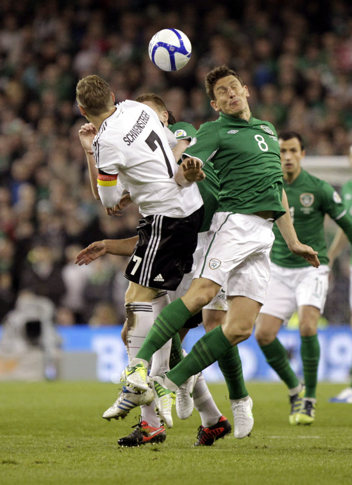 Photo -   Republic of Ireland's Keith Andrews, right, is challenged by Germany's Bastian Schweinsteiger during their World Cup Group C qualifying soccer match at the Aviva Stadium, Dublin, Ireland, Friday, Oct. 12, 2012. (AP Photo/Peter Morrison)
