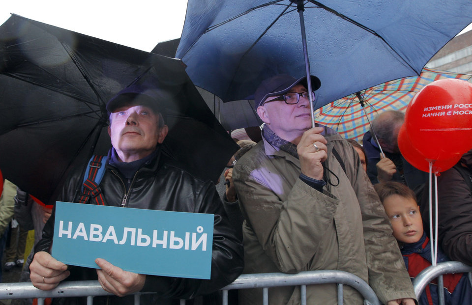 Photo - Supporters of Russian opposition leader Alexei Navalny attend his rally in rain-soaked Moscow, Russia, Friday, Sept. 6, 2013. The anti-corruption blogger and a leader of the Russian protest movement, Navalny will face the incumbent Mayor Sergei Sobyanin, in the upcoming Moscow's mayoral election on Sept. 8. The sign reads Navalny. (AP Photo/Sergei Grits)