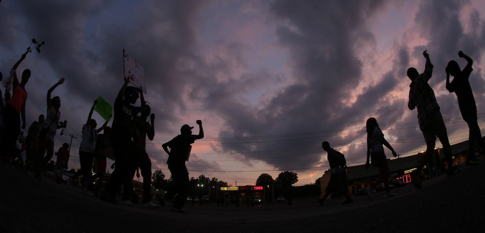 Photo - In this photo taken with a fisheye lens, people protest Monday, Aug. 18, 2014, for Michael Brown, who was killed by police Aug. 9 in Ferguson, Mo. Brown's shooting has sparked more than a week of protests, riots and looting in the St. Louis suburb. (AP Photo/Charlie Riedel)