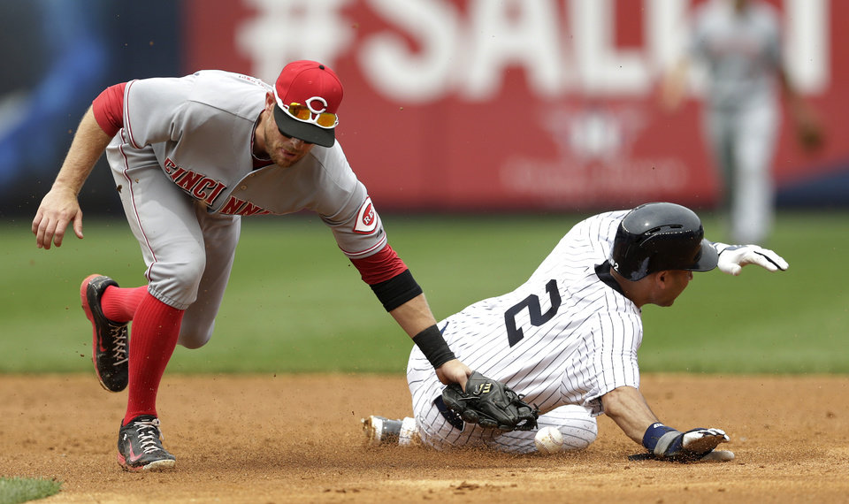 Photo - New York Yankees' Derek Jeter (2) steals second base as Cincinnati Reds shortstop Zack Cozart misses the ball while making the tag during the fifth inning of a baseball game, Saturday, July 19, 2014, at Yankee Stadium in New York. (AP Photo/Julio Cortez)