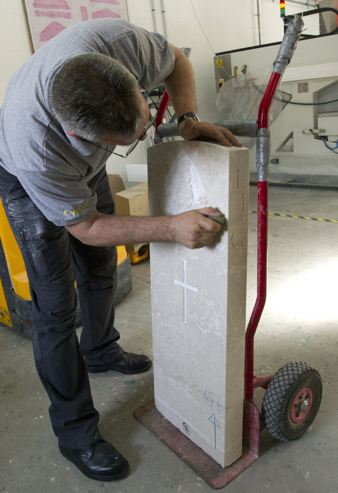 Photo - A worker rubs grit off of a newly engraved headstone of a WWI soldier at the workshop of the Commonwealth War Graves Commission in Beaurains, France, on Wednesday, April 17, 2013. As Commonwealth cemeteries and monuments around the world are currently being renovated in preparation for centenary events the manufacturing and engraving of new headstones plays an integral part of the process. (AP Photo/Virginia Mayo)