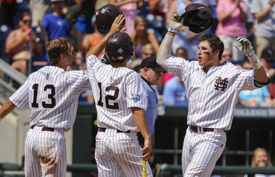 Photo - Mississippi State's Hunter Renfroe, right, celebrates with teammates Brett Pirtle, left, and Adam Frazier (12) after hitting a three-run home run against Oregon State in the fifth inning of an NCAA College World Series baseball game in Omaha, Neb., Friday, June 21, 2013. (AP Photo/Francis Gardler)