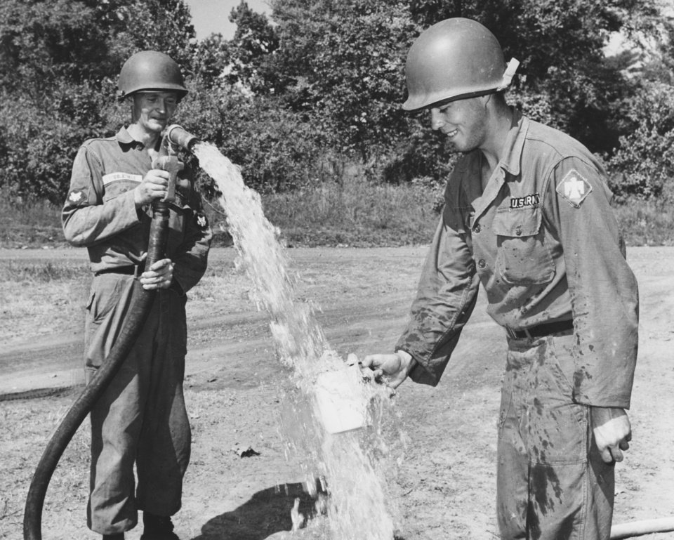 Photo - There's no water shortage for the 45th Infantry Division at Fort Chaffee, Ark.  The 120th Engineers' water purification center can produce 1,500 gallons of drinking water an hour at a lake miles from the main post.  S-4 Dan Stubblefied, Mustang, fills a thirsty Thunderbird's cup.  Staff photo by George Tapscott.  Photo dated 08/13/1963 and published on 08/15/1963 in The Oklahoma City Times (LS).