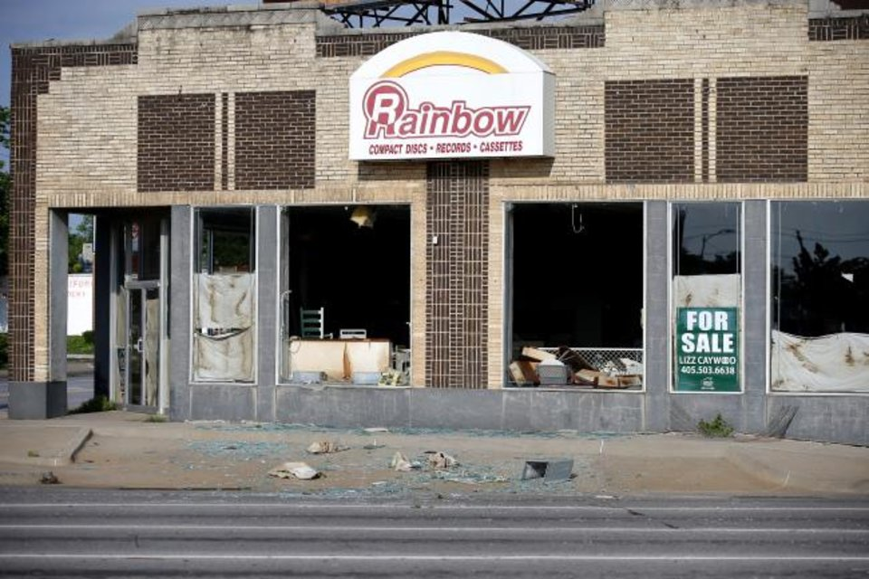 Photo -  Plate glass windows were blown out of the former Rainbow music store at NW 23 and Classen Boulevard by Saturday's storm. [Sarah Phipps/The Oklahoman]