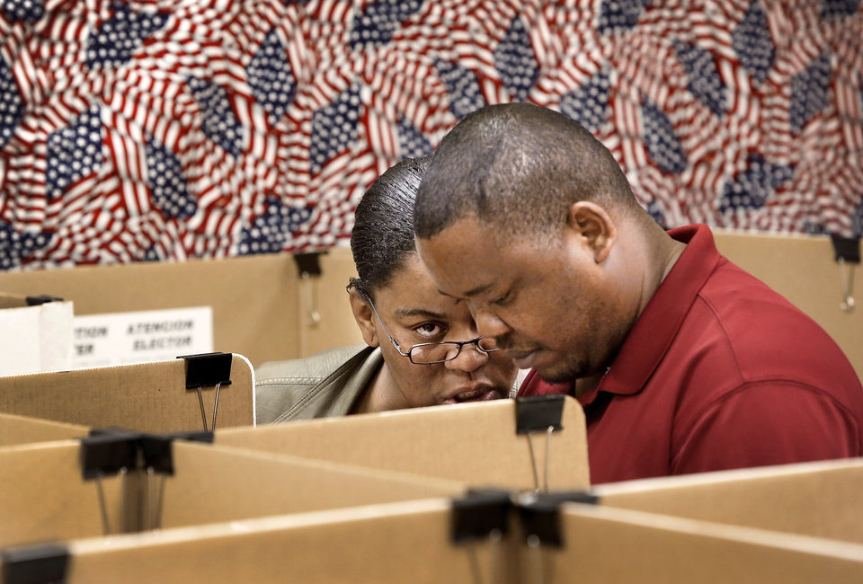 Rogenia Osita leans over to assist her husband, Chukwudi Emmanuel Osita, as he marks his ballot as the couple joined hundreds of other early voters inside the Oklahoma County Election Board on N. Lincoln Blvd, Monday afternoon, Nov. 5, 2012. It was Chukwudi\'s first time to vote in a U.S. presidential election since becoming a naturalized citizen from his native country of Nigeria. Rogenia is a native Oklahoma, having been raised in Idabel. The couple now lives in Oklahoma City. Chukwudi said his wife helped him with the wording on the ballot, especially the state questions. He laughed when he admitted his wife tried to tell him how to vote, but he explained that he insisted on making up his own mind. His wife nodded her head in agreement, but laughed, too. Photo by Jim Beckel, The Oklahoman