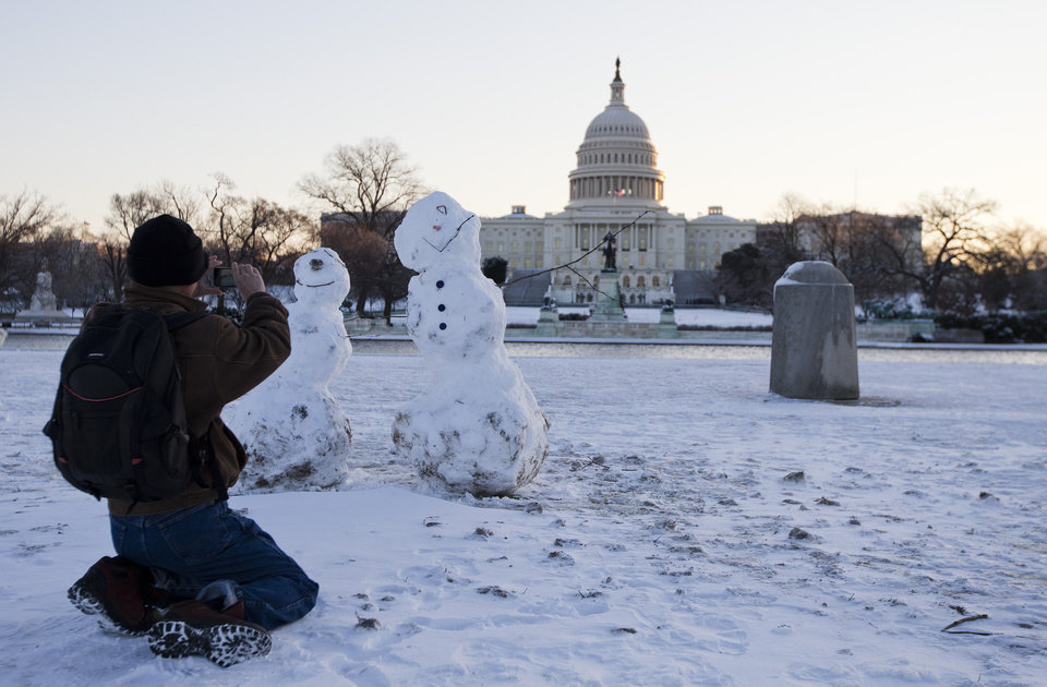 Photo - A man takes photos of snowmen with the Capitol in the background, Friday, Jan. 3, 2014, in Washington. After a storm blew through the Washington region overnight, roads are being cleared and many schools systems are closed. The federal government and the District of Columbia government will be open Friday, but workers have the option to take leave or telework.  (AP Photo/ Evan Vucci)