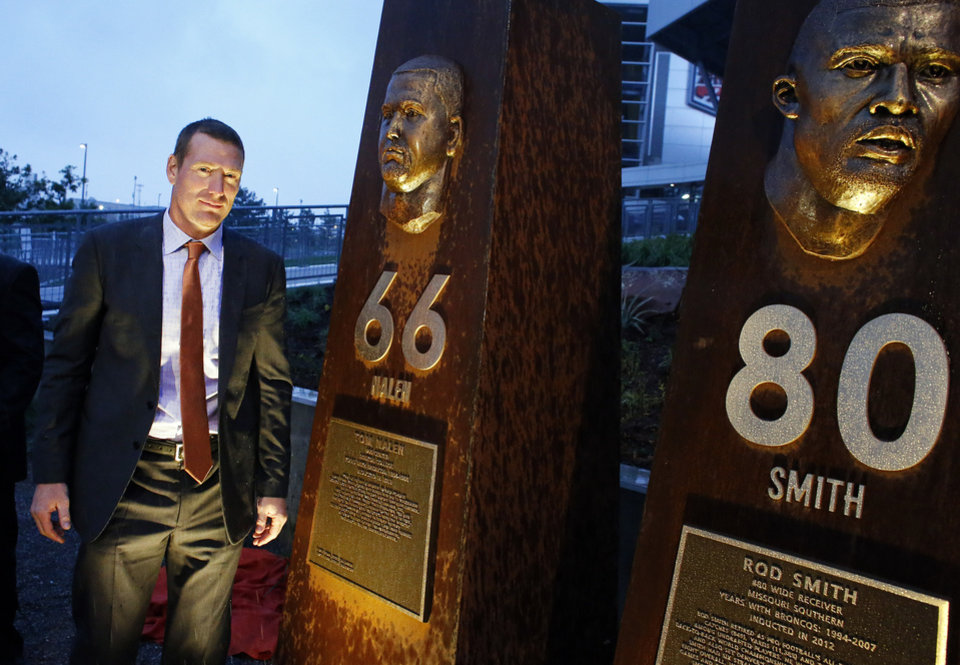 Photo - Former Denver Broncos center Tom Nalen stands in front of a pillar bearing his likeness, alongside those for fellow Bronco greats, at the unveiling ceremony for the Broncos Ring of  Fame Plaza, at Mile High Stadium on Friday Sept. 27, 2013, in Denver. Nalen is to be inducted into Ring of Fame this weekend. (AP Photo/Brennan Linsley)