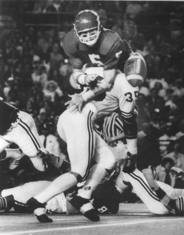 Former OU quarterback Steve Davis makes a pitch just as Michigan's Don Dufek makes a hit during the 1976 Orange Bowl. OKLAHOMAN ARCHIVE PHOTO
