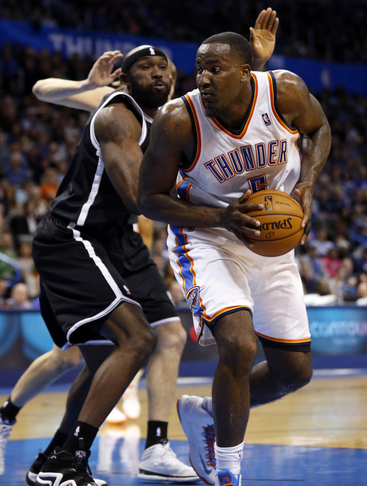 Photo - Thunder's Serge Ibaka (9) is fouled by Brooklyn's Reggie Evans in the second half of an NBA basketball game where the Oklahoma City Thunder were defeated 95-93 by the Brooklyn Nets at the Chesapeake Energy Arena in Oklahoma City, on Thursday, Jan. 2, 2014. Photo by Steve Sisney The Oklahoman
