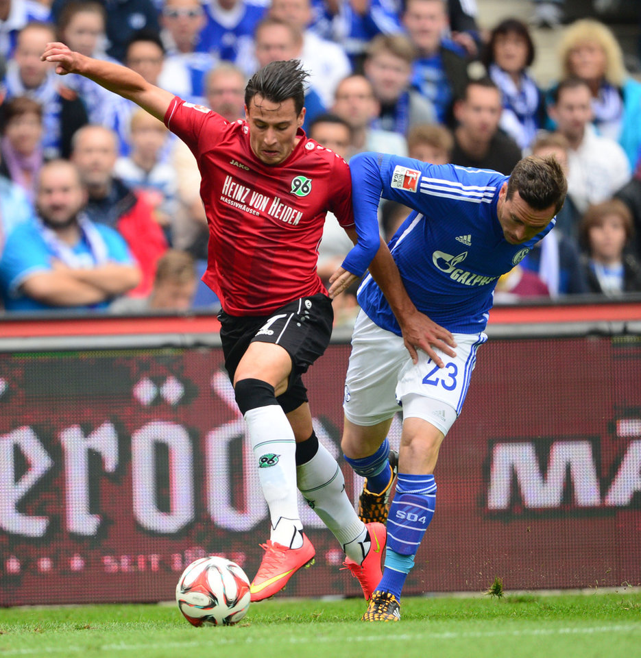 Photo - Hannover's Edgar Prib , left, and Schalke's Christian Fuchs  challenge for the ball during the German Bundesliga soccer match between Hannover 96 and Schalke 04 in Hannover, northern Germany, Saturday Aug. 23, 2014.  (AP Photo/dpa, Peter Steffen)