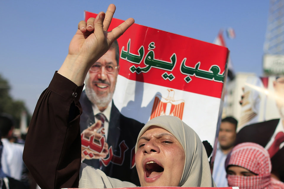 Supporters of Egypt\'s Islamist President Mohammed Morsi chant slogans during a rally, in Nasser City, Cairo, Egypt, Thursday, July 4, 2013. The chief justice of Egypt\'s Supreme Constitutional Court was sworn in Thursday as the nation\'s interim president, taking over hours after the military ousted the Islamist President Mohammed Morsi. Adly Mansour took the oath of office at the Nile-side Constitutional Court in a ceremony broadcast live on state television. According to military decree, Mansour will serve as Egypt\'s interim leader until a new president is elected. A date for that vote has yet to be set. Arabic reads,