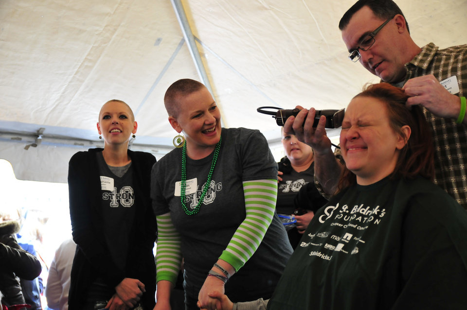 Beth McDowell, center, holds the hand of Jessica Maynard, both members of the 10 Strong team, as Jessica gets her head shaved for the St. Baldrick's charity at VZD's Restaurant and Club in Oklahoma City, Okla. Sunday, March 23, 2013.  Photo by Nick Oxford, for The Oklahoman