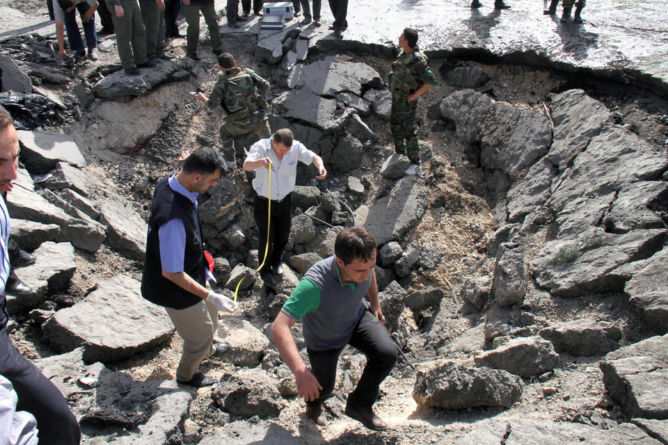 Photo - Syrian inspectors investigate the crater in front of a damaged military intelligence building where two bombs exploded, at Qazaz neighborhood in Damascus, Syria, on Thursday May 10, 2012. Two strong explosions ripped through the Syrian capital Thursday, killing or wounding dozens of people and leaving scenes of carnage in the streets in an assault against a center of government power. (AP Photo/Bassem Tellawi) ORG XMIT: BEI120
