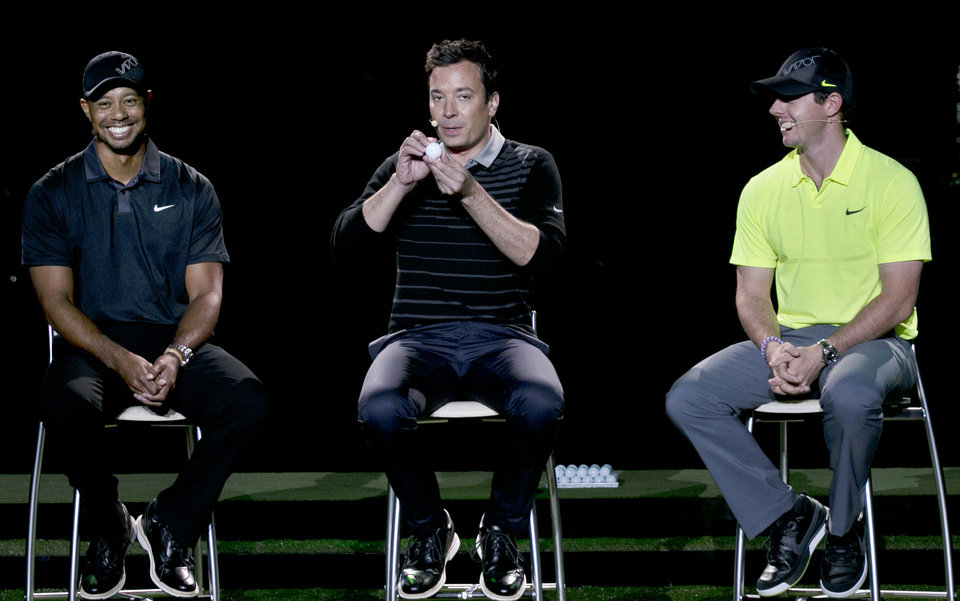 Photo - Golfers Tiger Woods, left, and Rory McIlroy right, sit near as television host Jimmy Fallon makes a joke during a golfing demonstration, Monday, Aug. 18, 2014, in Jersey City, N.J.  (AP Photo/Mel Evans)
