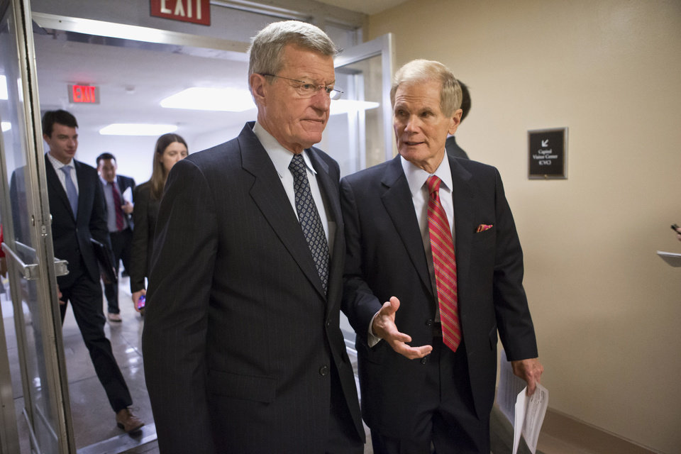 Photo - Senate Finance Committee Chairman Sen. Max Baucus, D-Mont., left, and Sen. Bill Nelson, D-Fla., right, join other senators in the rush to the Senate floor on Capitol in Washington, Wednesday, July 10, 2013, for a vote to end debate on the Democrats' plan to restore lower interest rates on student loans one week after Congress' inaction caused those rates to double. The White House and most Senate Democrats favored restoring interest rates on subsidized Stafford loans to 3.4 percent for another year, but lawmakers failed to muster the necessary 60 votes to overcome a procedural hurdle.  (AP Photo/J. Scott Applewhite)