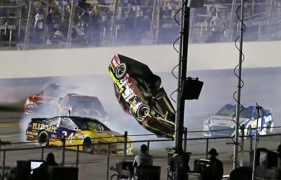 Photo - Clint Bowyer (15) flips upside down as he is involved in a multi-car crash with David Ragan (34) and others on the final lap of the second of two NASCAR Sprint Cup qualifying auto races at Daytona International Speedway in Daytona Beach, Fla., Thursday, Feb. 20, 2014. (AP Photo/John Raoux)