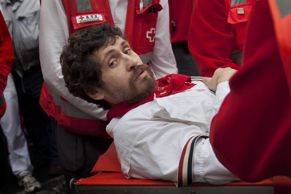 Photo - U.S. runner Bill Hillmann, 35, from Chicago, Ill., is carried on a stretcher after being gored on his right leg by a Victoriano del Rio ranch fighting bull during the running of the bulls at the San Fermin festival in Pamplona, Spain, Wednesday, July 9, 2014. A journalist and author, Hillmann, is a veteran San Fermin runner and has written many pieces about the festival. The injury was said to be serious but his life was not in any danger. Revelers from around the world arrive in Pamplona every year to take part on some of the eight days of the running of the bulls glorified by Ernest Hemingway's 1926 novel