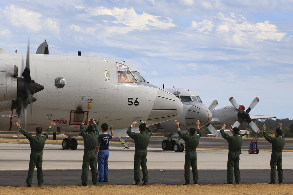 Photo - Japan Maritime Self-Defense Force farewell their P-3C Orion as it taxis from the Royal Australian Air Force Pearce Base to commence a search for possible debris from the missing Malaysia Airlines flight MH370, in Perth, Australia, Monday, March 24, 2014. Satellite images released by Australia and China had earlier identified possible debris in an area that may be linked to the disappearance of the flight on March 8 with 239 people aboard. (AP Photo/Paul Kane, Pool)
