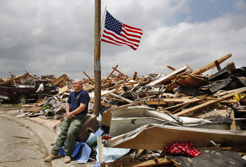 Photo - Oklahoma City police Sgt. Cody Koelsch sits on the top half of his broken brick mailbox in front of his home at 14701 S Harvey.  His home was reduced to a small mountain of debris after taking a direct hit in the May 20 EF5 tornado. Koelsh survived the tornado in his storm shelter with his wife, Amanda, and their 5 week-old daughter, Saylor.   Photo  by Jim Beckel, The Oklahoman.  Jim Beckel - THE OKLAHOMAN