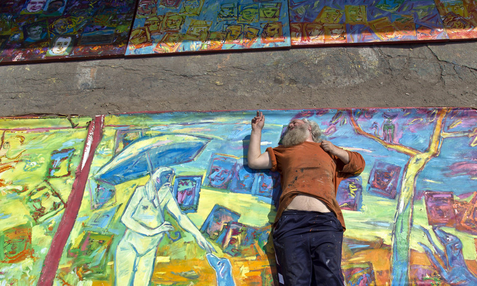 Photo - In this photo taken on April 4, 2013, Romanian artist Vasile Muresan-Murivale poses on one of his paintings in a parking lot,  in Bucharest, Romania. The white-bearded painter can often be seen sitting on his colorful canvasses which he displays in the street followed by the street dogs which are his companions and also inspire his work. The 56-year-old, whose home city is Bistrita_the Transylvanian town associated with the legendary Count Dracula_ has been painting with passion since he was a teen, producing vivid works of Monaco, the streets of Paris, the hurly burly of the Romanian capital and huge colorful more abstract canvasses. (AP Photo/Vadim Ghirda)