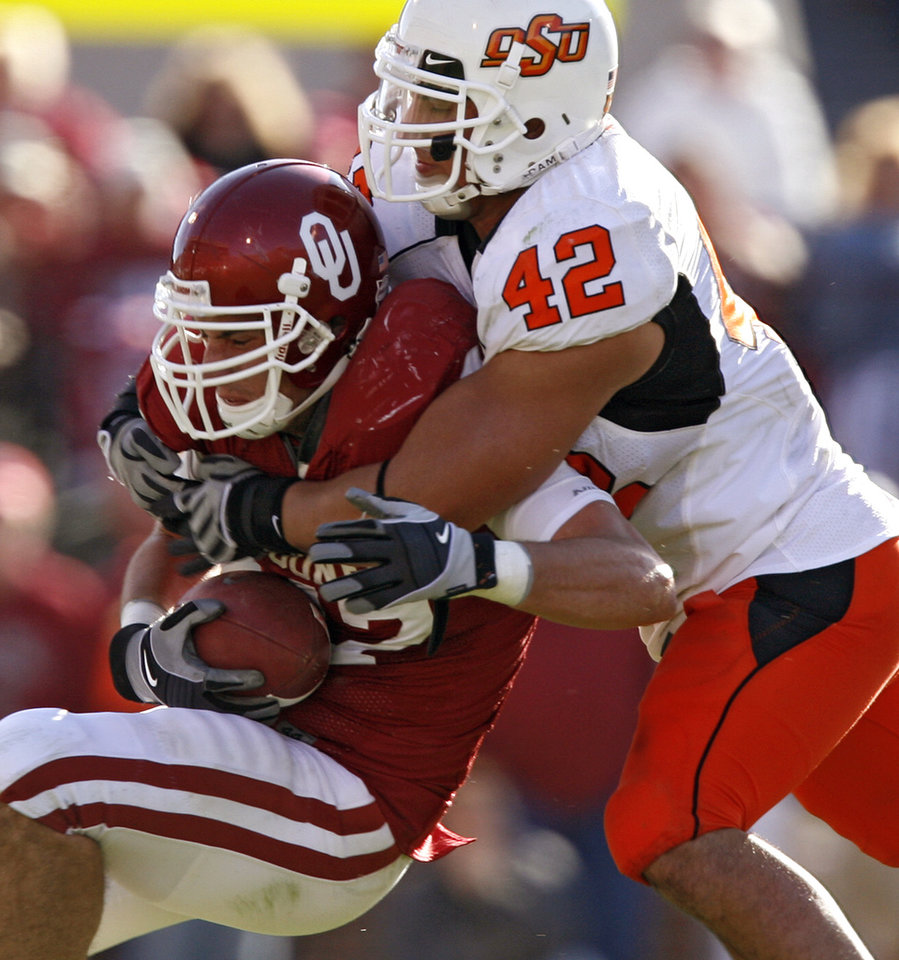 Photo - OSU's Justin Gent (42) brings down Oklahoma's Trent Ratterree (47) during the second half of the Bedlam college football game between the University of Oklahoma Sooners (OU) and the Oklahoma State University Cowboys (OSU) at the Gaylord Family-Oklahoma Memorial Stadium on Saturday, Nov. 28, 2009, in Norman, Okla.Photo by Chris Landsberger, The Oklahoman