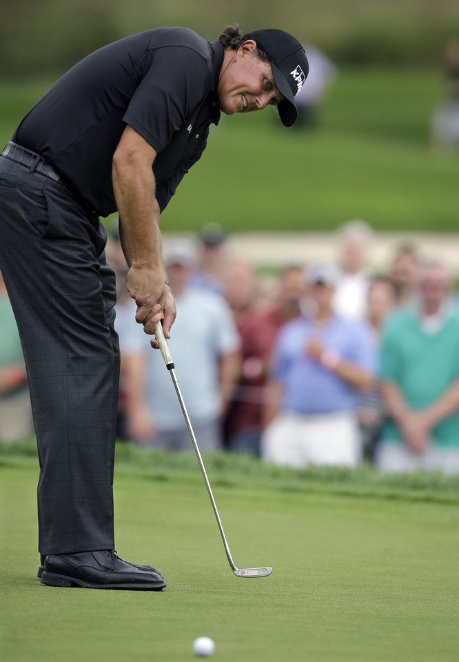 Photo - Phil Mickelson putts on the 15th hole during the second round of play at The Barclays golf tournament Friday, Aug. 22, 2014, in Paramus, N.J.  (AP Photo/Mel Evans)