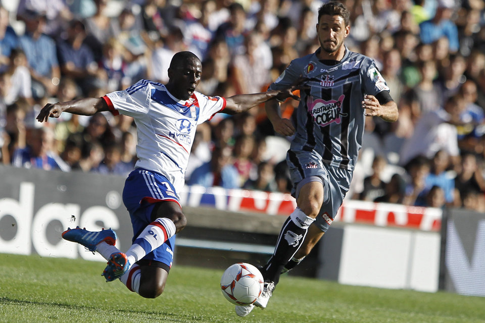 Photo -   Lyon's Mouhamadou Dabo, left, challenges for the ball with Ajaccio's Jean Baptiste Pierazzi during their French League One soccer match at Gerland stadium, in Lyon, central France, Sunday, Sept. 16, 2012. (AP Photo/Laurent Cipriani)