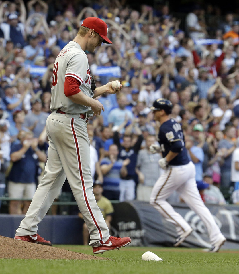 Photo - Philadelphia Phillies starting pitcher Kyle Kendrick looks down after giving up a grand slam to Milwaukee Brewers' Lyle Overbay, right, during the first inning of a baseball game Tuesday, July 8, 2014, in Milwaukee. (AP Photo/Morry Gash)