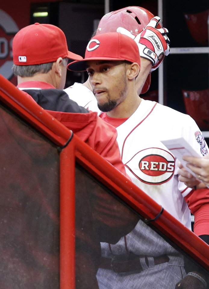 Photo - Cincinnati Reds center fielder Billy Hamilton, right, talks with manager Bryan Price in the dugout after being taken out in the first inning of a baseball game against the Milwaukee Brewers, Thursday, May 1, 2014, in Cincinnati. Hamilton injured a hand making a diving catch on a fly ball hit by Carlos Gomez. (AP Photo/Al Behrman)