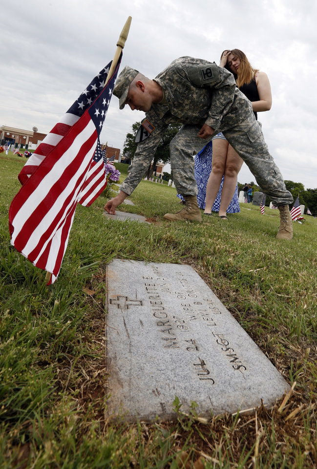 Army Reserve Sgt Roger Elder, who saw service in Bosnia and Korea, places pennies on gravestones to show his respects before a Memorial Day ceremony for Daughters of Union Veterans on May 26, 2014 in Oklahoma City, Okla. Elder\'s daughter Kadie (right), 19, found the tradition and suggested it to her dad. Photo by Steve Sisney, The Oklahoman