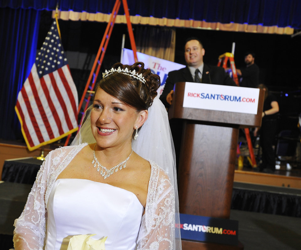 Sarah Heath, left, poses for a wedding photographer on her wedding day as Rick Santorum campaign volunteer Mike Rendino looks on at the podium before a primary elections party at the Citadel in Charleston, S.C., Saturday, Jan. 21, 2012. (AP Photo/Rainier Ehrhardt) ORG XMIT: SCRE103