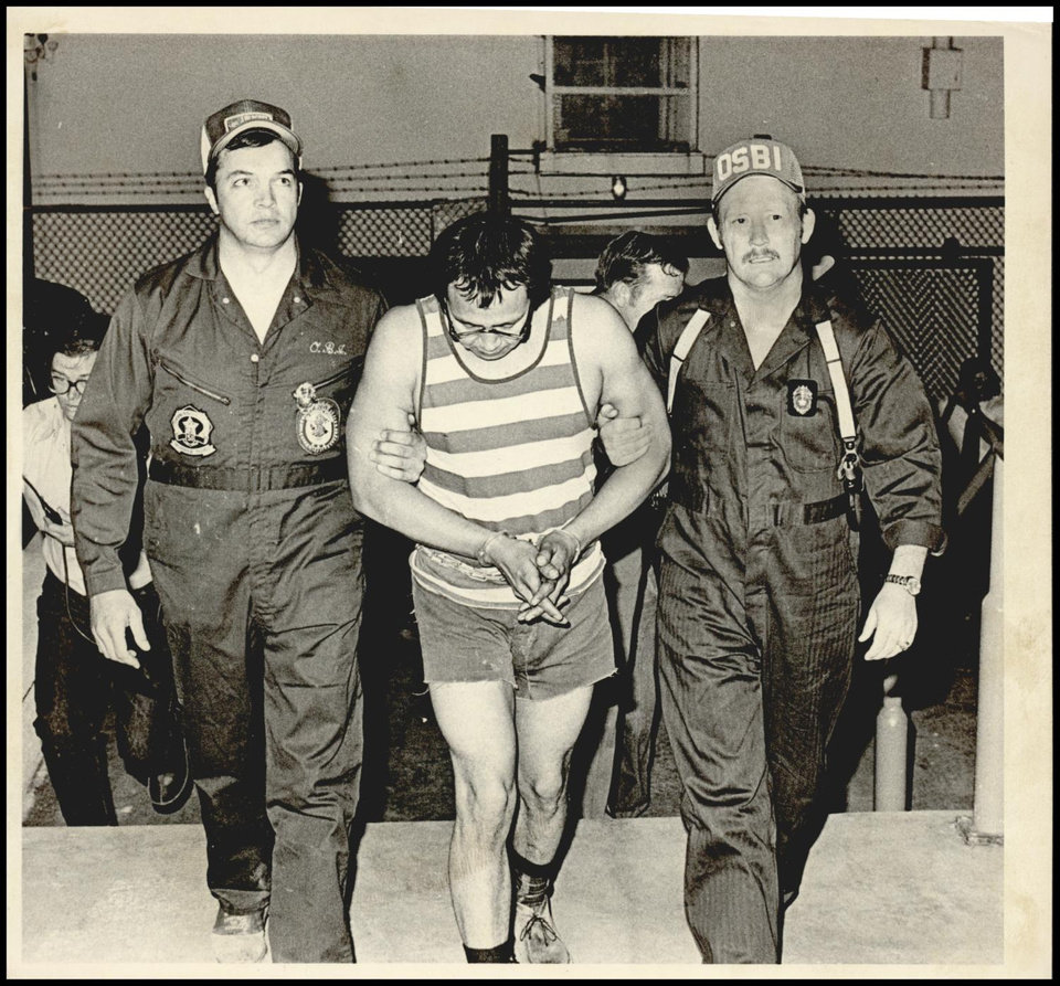 Photo -  Gene Leroy Hart, center, is escorted by OSBI agents.