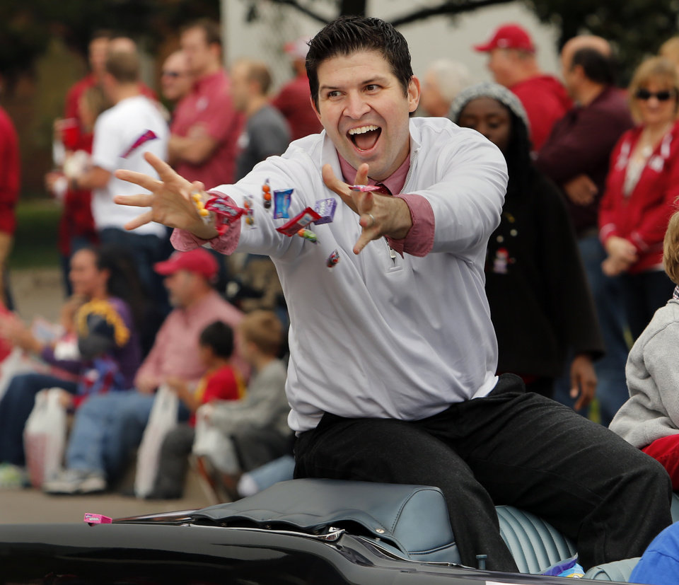 College of Business dean Daniel Pullin tosses candy to the crown during the Homecoming Parade before the  college football game between the University of Oklahoma Sooners (OU) and the Texas Tech Red Raiders at Gaylord Family-Oklahoma Memorial Stadium in Norman, Okla., on Saturday, Oct. 26, 2013. Photo by Steve Sisney, The Oklahoman